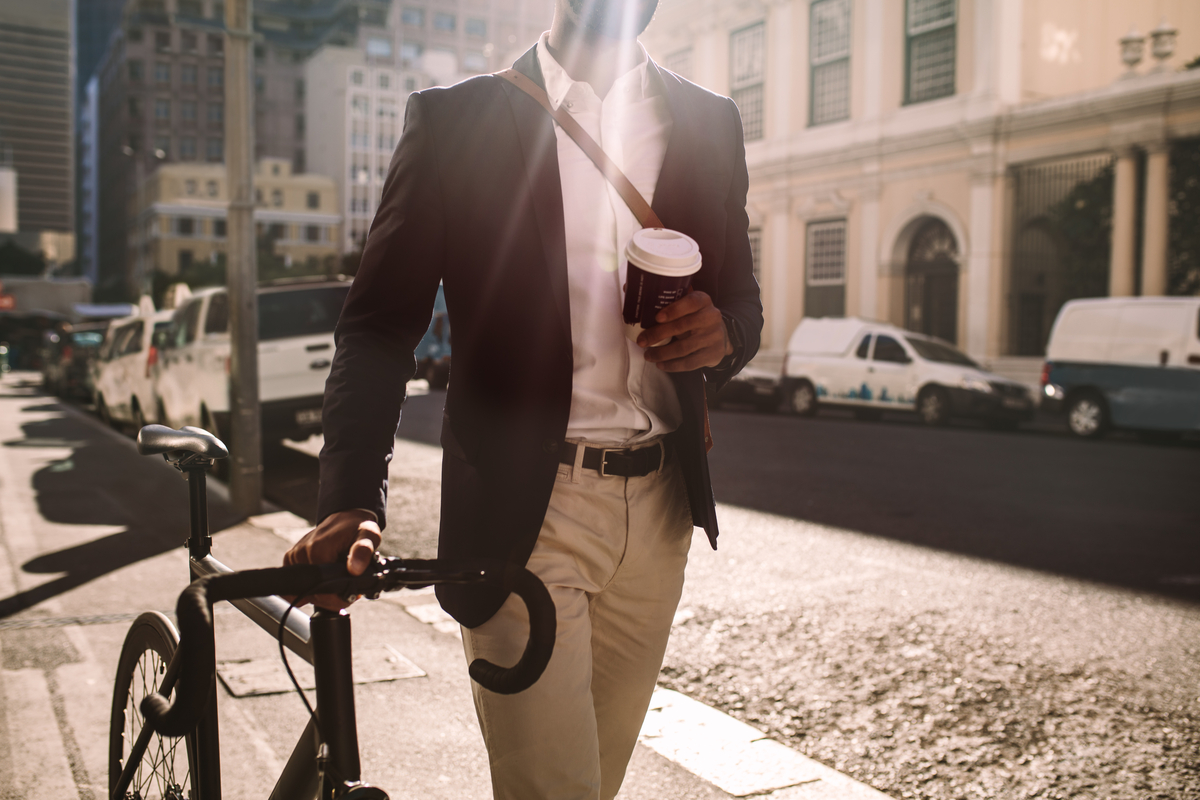 Man walking with bike and holding coffee.