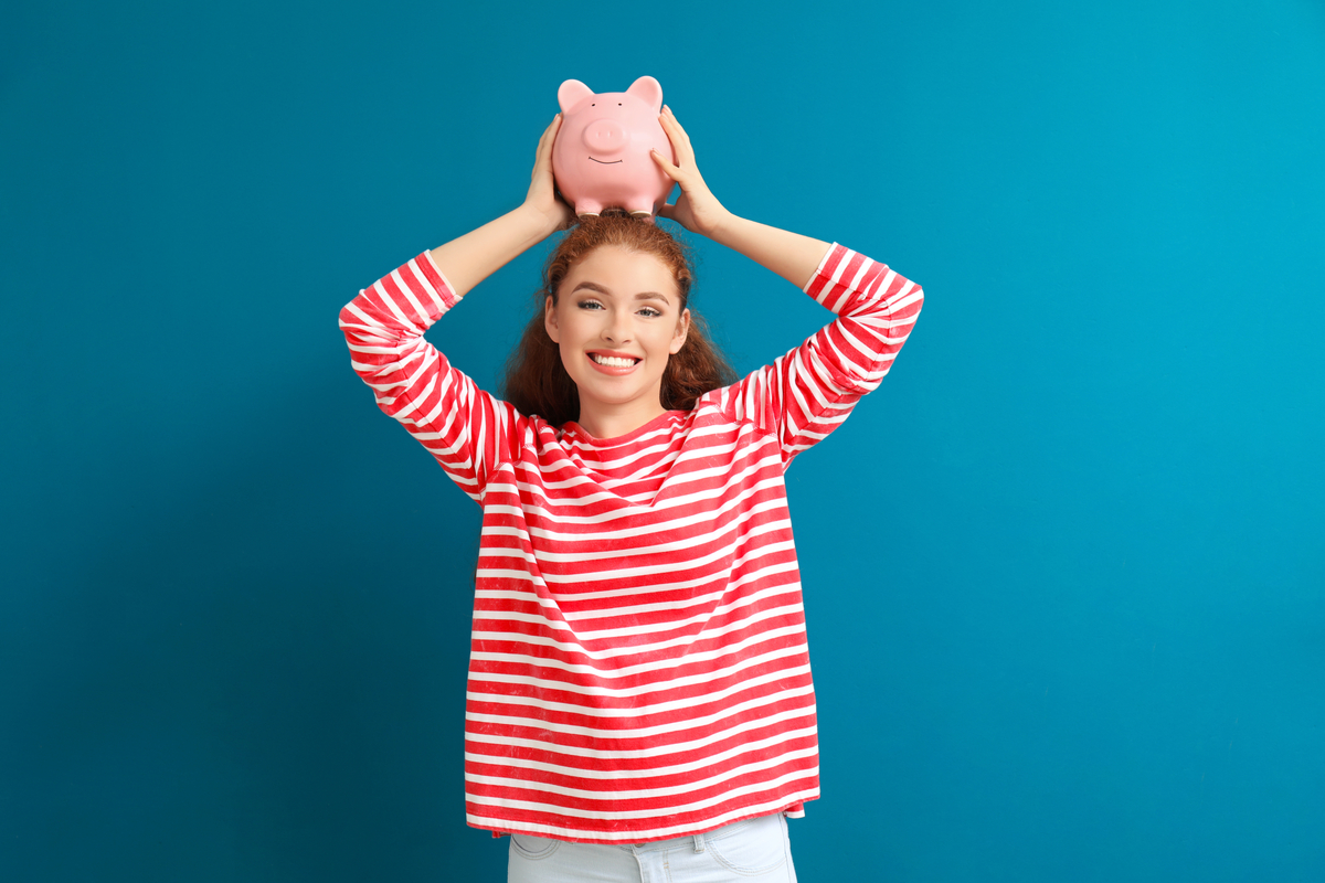 Woman holding a piggy bank on her head.