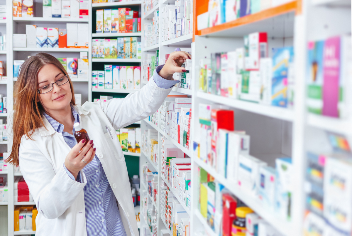 Pharmacist pulling orders from the shelf.